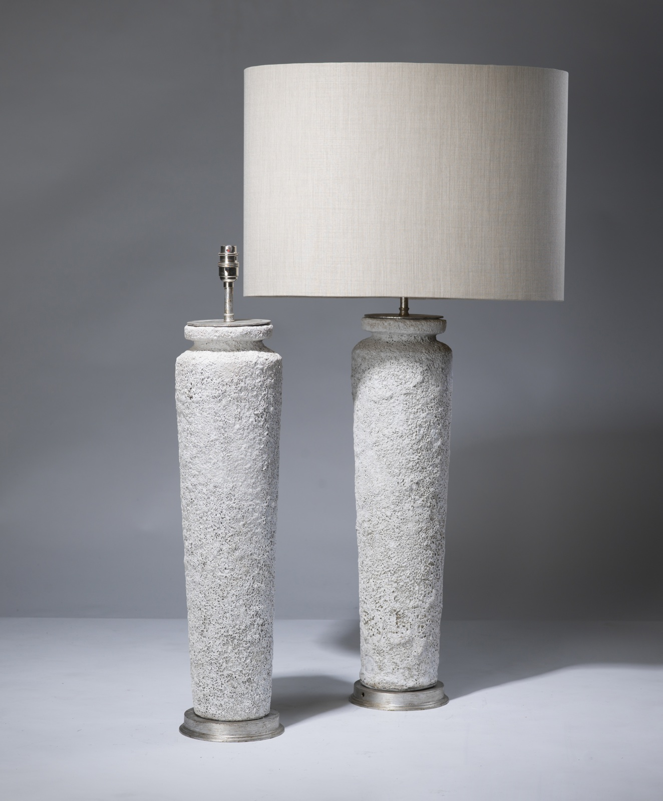 pair of large white ceramic lamps on distressed silver leaf bases