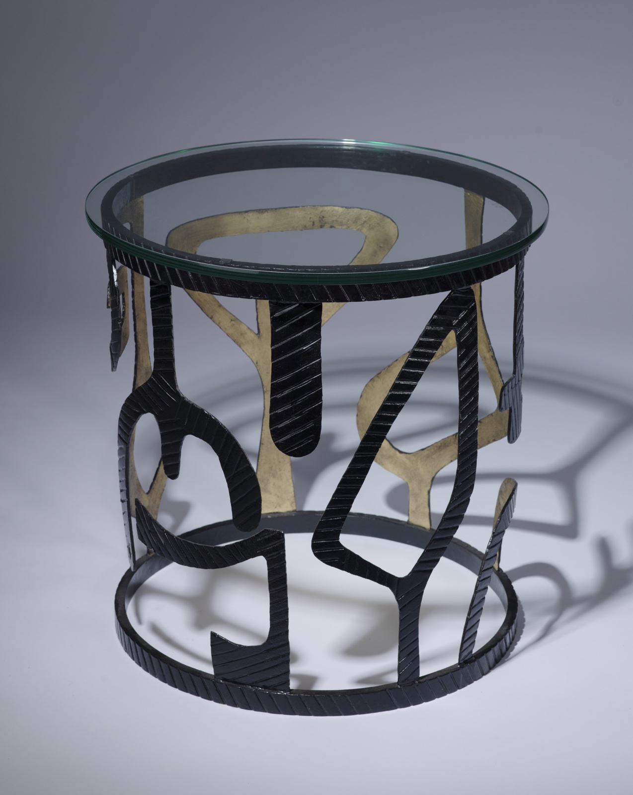 wrought iron 'miro' side table in black, gold finish with glass top