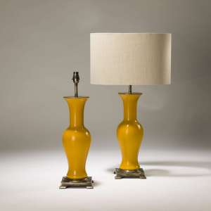 Pair of medium yellow glass column lamps on distressed brass bases (T3731)