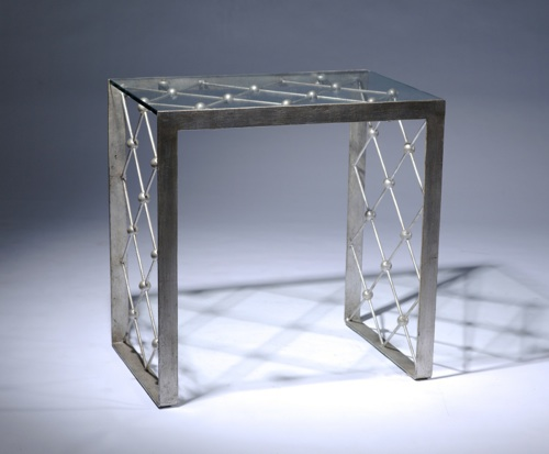 Wrought iron net side table in warm distressed silver leaf finish with glass top