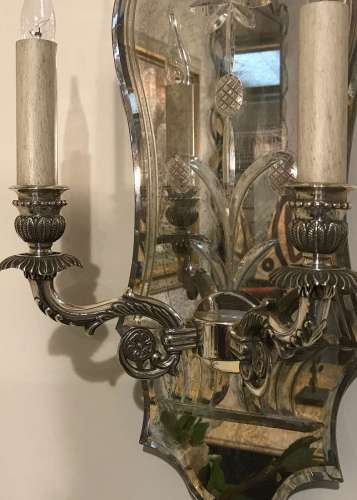 Pair of mirror backed wall lights with silver plated bronze arms