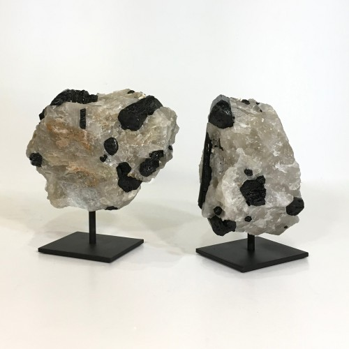pieces of rough clear quartz with black minerals on metal stands