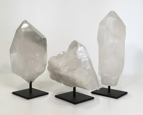 pieces of polished clear quartz on metal stands