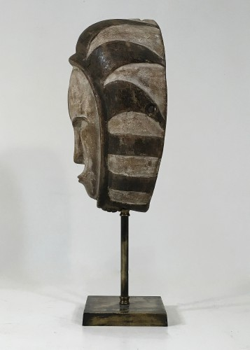 antique wooden tribal mask on antique brass stand