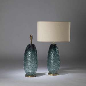 Pair of small teal green blue 'molten' almond glass lamps on round brass bases (T4434)